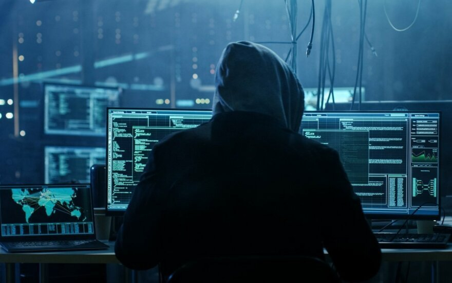 A hacker in a hoodie in front of several monitors